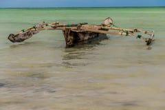 Un barco de madera hecho en casa viejo en el oc?ano contra el horizonte fotografía de archivo libre de regalías