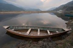 Un barco de madera viejo grande a través de la orilla en el lago Feva, el agua refleja un cielo gris melancólico, en el fondo de  Fotografía de archivo libre de regalías