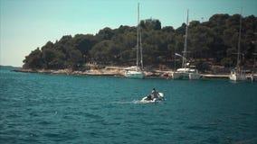 Un barco de motor se mueve a través de las ondas a la orilla almacen de metraje de vídeo