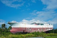 Un barco de pesca abandonado en la hierba con el cielo azul Foto de archivo libre de regalías