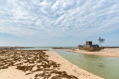 Un barco de pesca abandonado en una playa con las algas secas En la isla de Weizhou, Guangxi, China Foto de archivo libre de regalías