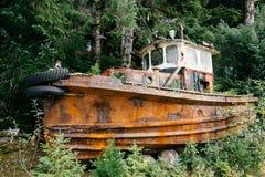 Un barco de pesca abandonado oxidado por los árboles imágenes de archivo libres de regalías