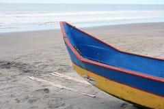 Barco de pesca azul y amarillo en una playa Foto de archivo libre de regalías