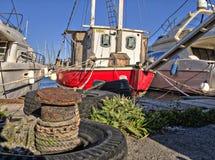 Un barco de pesca rojo amarrado al muelle; el oxidado, bolardo del metal que se amarra a puede ser visto en el primero plano Imagenes de archivo