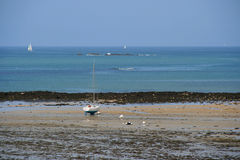 Un barco de placer blanco y azul se trenza en una playa (Francia) Fotografía de archivo
