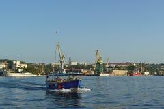 Un barco de placer con los turistas navega en la bahía de Sevastopol En la orilla del puerto el cargo cranes Fotografía de archivo libre de regalías