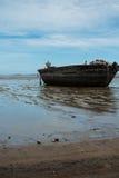 Un barco de rowing viejo necesitando la reparación en la playa imagen de archivo