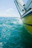 Un barco de vela amarillo de inclinación imagenes de archivo