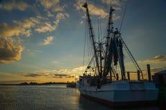 Un barco del camarón atado a un embarcadero en la puesta del sol fotografía de archivo libre de regalías