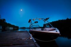 Un barco del wakeboard atracó en el lago José por la tarde con la luna en el fondo foto de archivo libre de regalías