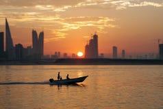 Un barco durante puesta del sol con los edificios de highrise de Bahrein Imagenes de archivo