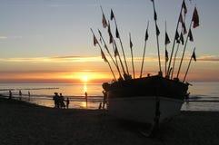 Un barco en la costa durante la puesta del sol Foto de archivo