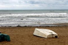 Un barco es al revés en la arena de la playa con un fondo del mar en un día nublado Fotos de archivo