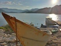 Un barco oxidado cerca del lago Imagen de archivo libre de regalías