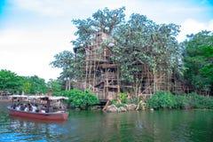 Un barco por completo de los pasajeros que viajan a través del río alrededor de la casa en el árbol de Tarzan en Hong Kong imagen de archivo libre de regalías