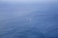 Un barco solitario que navega el océano foto de archivo