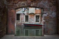 Un barco veneciano vibrante enmarcado por un pequeño de la calle en Venecia, Italia Fotos de archivo libres de regalías