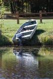 Un barco y un motor viejos en la orilla de un lago Imagen de archivo