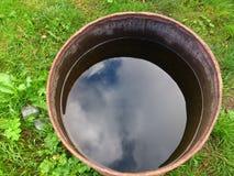 Un baril de l'eau sur l'herbe Vue de ci-avant Le ciel est reflété dans un baril de l'eau images libres de droits