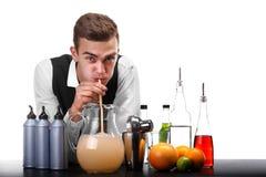 Un barista bello che beve una limonata ad un contatore della barra, arance, calce, un agitatore isolato su un fondo bianco immagine stock