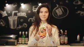 Un barista femenino joven hermoso que prueba un mojito de la fresa almacen de metraje de vídeo