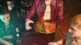 Un barista maschio del cameriere porta un cocktail dell'alcool ad una società di giovani amici stock footage