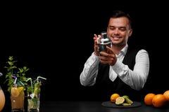 Un barista pulisce un agitatore al contatore della barra, il limone, la calce, le arance, cocktail su un fondo nero Fotografie Stock