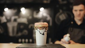 Un barista que pone un buñuelo encima de un batido de leche en una taza plástica y que lo adorna con crema azotada metrajes