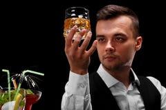 Un barman attirant tient un verre de whiskey, verres de margarita sur un compteur de barre sur un fond noir Images libres de droits