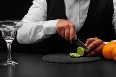 Un barman coupe une chaux verte pour des tranches avec un couteau, un compteur de barre avec des oranges sur un fond noir Photographie stock