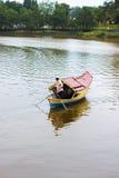 Un barquero del local cruza el río para coger a los clientes. Fotografía de archivo libre de regalías