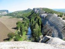 Un barranco profundo con paredes de piedra y un río abajo Imagenes de archivo