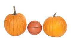 Un basket-ball en cuir entre la récolte Halloween de chute de deux potirons Photo stock