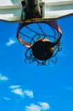 Un basket-ball entrant dans le filet Images stock