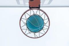 Un basket-ball passe par le filet, sur un terrain de jeu de voisinage photo libre de droits