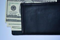 un bastone di 100 banconote in dollari da un portafoglio nero Immagini Stock