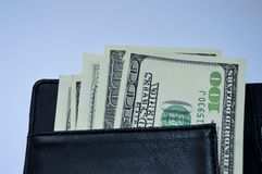 un bastone di 100 banconote in dollari da un portafoglio nero Immagini Stock Libere da Diritti