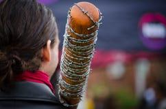 Un bate de béisbol de madera cubierto en alambre de púas en un hombro del hombre en los eventos anuales del paseo del zombi en pr fotos de archivo libres de regalías