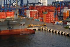 Un bateau étant déchargé, camions, récipients, et grues Photographie stock