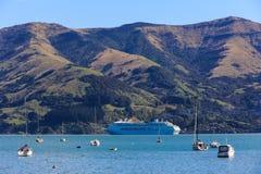 Un bateau de croisière ancré sur un fond montagneux images libres de droits