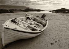 Un bateau de pêche attend la marée haute dans une baie scénique dans le Donegal Photographie stock