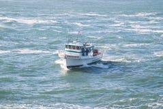 Un bateau de pêche professionnelle entrant dans le port Images libres de droits