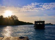 Un bateau de pêche retournant au dock avec le coucher du soleil sur son dos dans la station de vacances de hithi de bodu de Cocos photographie stock libre de droits