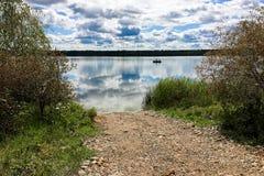 Un bateau de pêche silhouetté sur un lac calme Photographie stock libre de droits