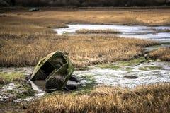 Un bateau de rangée vert coulé dans l'eau à un marais sur la côte de Kent image stock