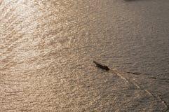 Un bateau en rivière avec la lumière de coucher du soleil photos stock