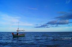 Un bateau isolé sous le ciel bleu en mer bleue Photos stock