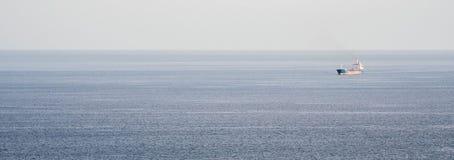 Un bateau isolé sur la mer Photographie stock