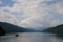 Un bateau navigue entre les montagnes Photo stock