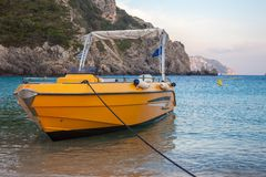 Un bateau privé jaune dans la plage L'amarrage de véhicule de l'eau de vitesse dans le rivage Une formation de roche montagneuse  images stock